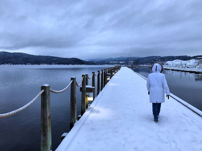 Rear view of woman walking on snow covered pier over frozen lake during winter