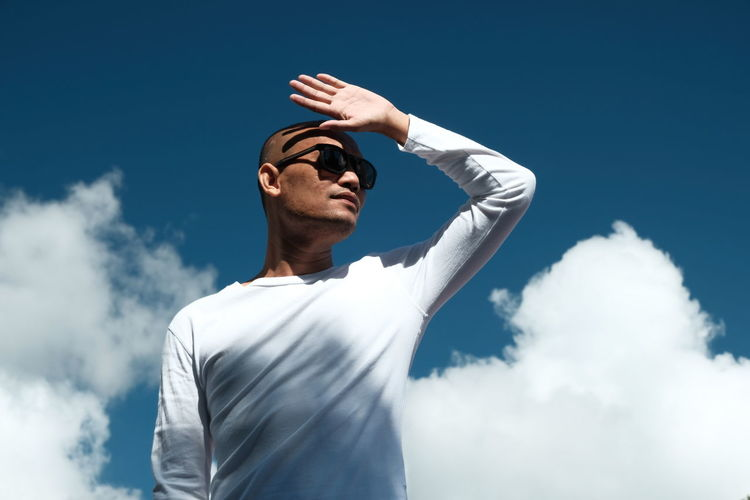 Low angle view of man standing against blue sky on a sunny day