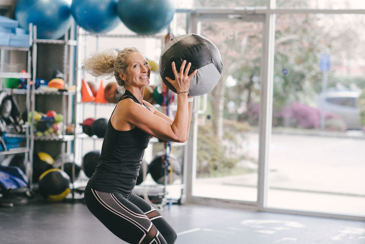 Portrait of smiling woman exercising with medicine ball while at gym