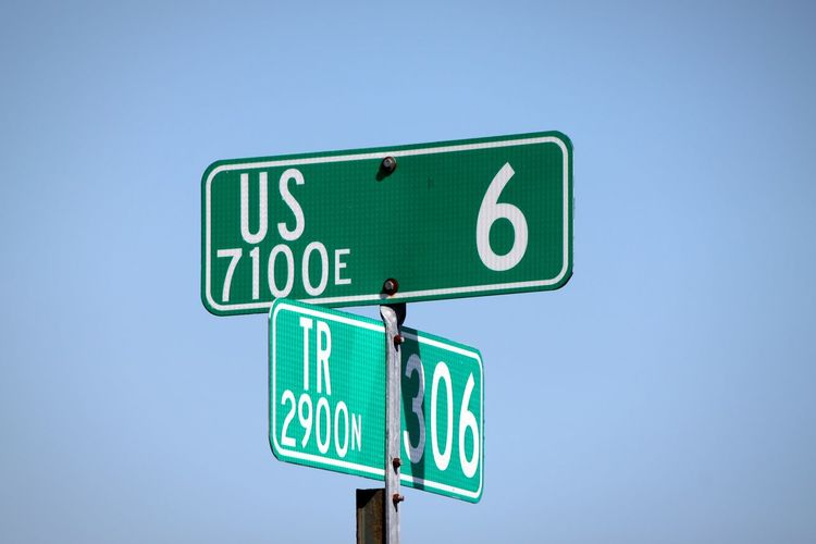 Low angle view of road signs against clear blue sky