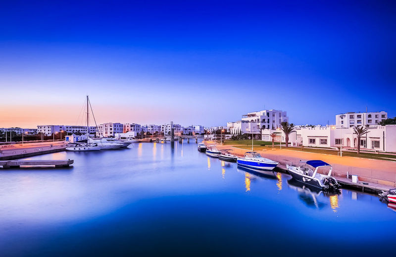 Boats moored at harbor in city against blue sky