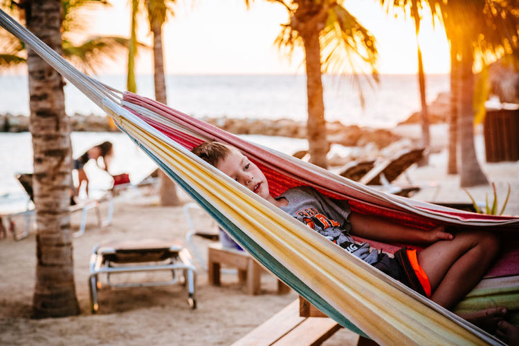 Young boy together in a hammock on the beach at blue bay in willemstad curacao Beach Beauty In Nature Chilling Day Hammock Outdoors People Relaxation Relaxing Sea Vacation Vacations