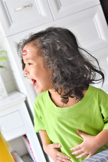 Cheerful girl with mouth open looking away at home