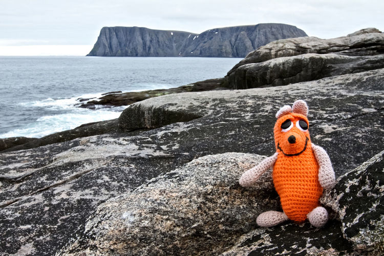 Toy On Rock Formation By Sea Against Sky