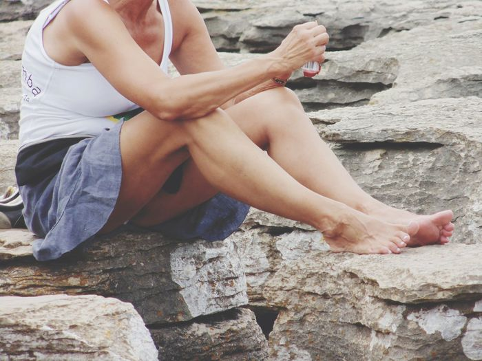 Midsection of woman sitting on rock