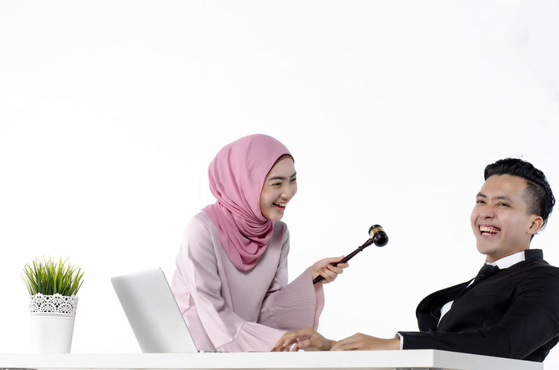 studio portrait of young hijab muslimah joking with her officemate, funny and happy moment Sitting Young Adult Two People Business Copy Space Communication Young Women Waist Up Occupation Smiling Technology Wireless Technology Real People Indoors  Office Men Table Women Young Men Business Person