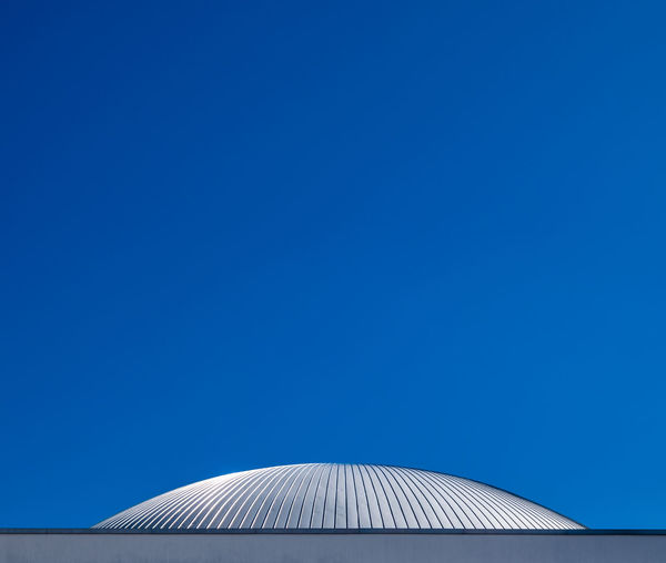 High section of modern building against clear blue sky