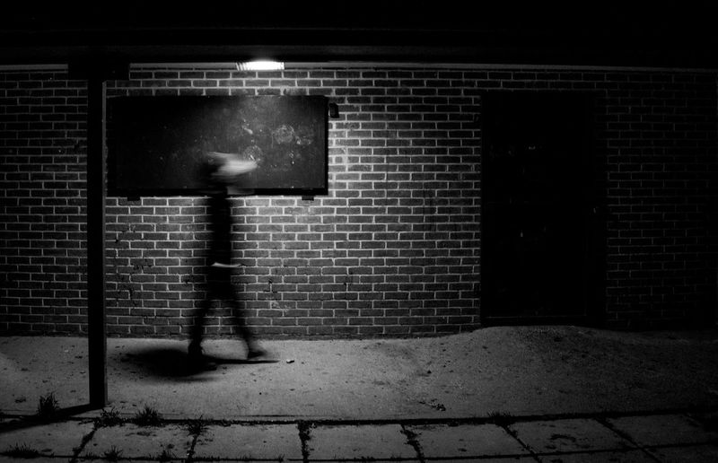 Shadow of man walking on footpath against building at night