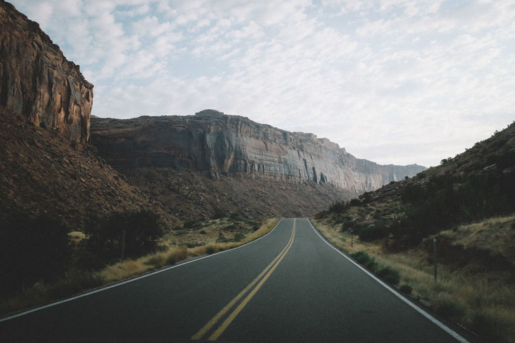 Empty road along rocky mountains
