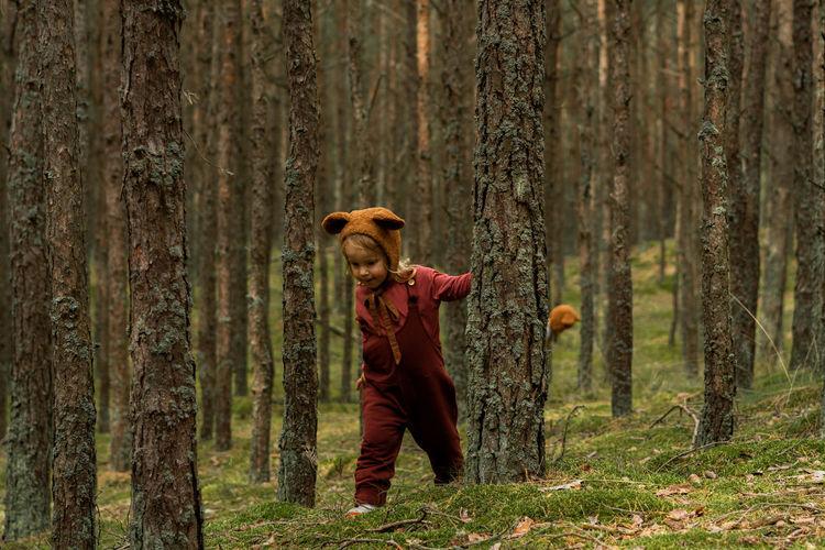 Toddler baby girl in bear bonnet walking in the woods