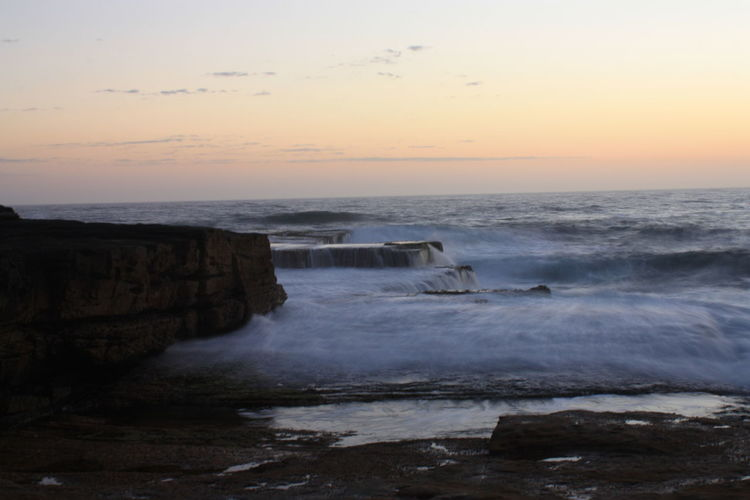 Rocks and waves at sunrise Beach Beauty In Nature Horizon Over Water Motion Nature No People Outdoors Scenics Sea Sky Sunrise Tranquil Scene Tranquility Water Wave