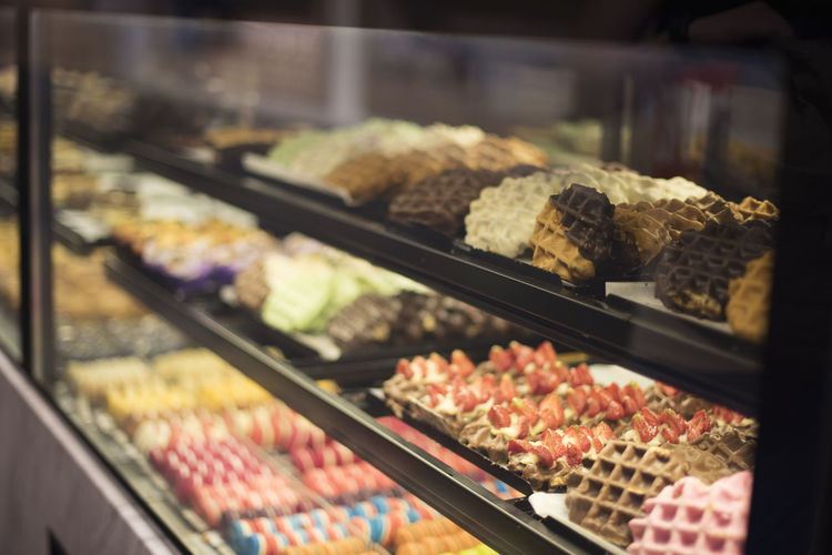 Various sweet food in display cabinet for sale at store