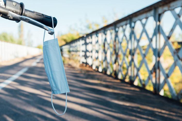 Close-up of metallic railing by bridge against sky