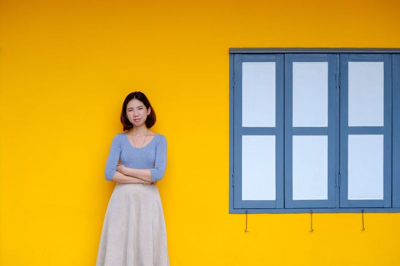 Portrait of young woman standing against yellow wall