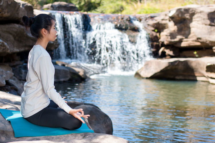 Side View Of Woman Doing Lotus Position Yoga While Sitting On Rocks Against Waterfall