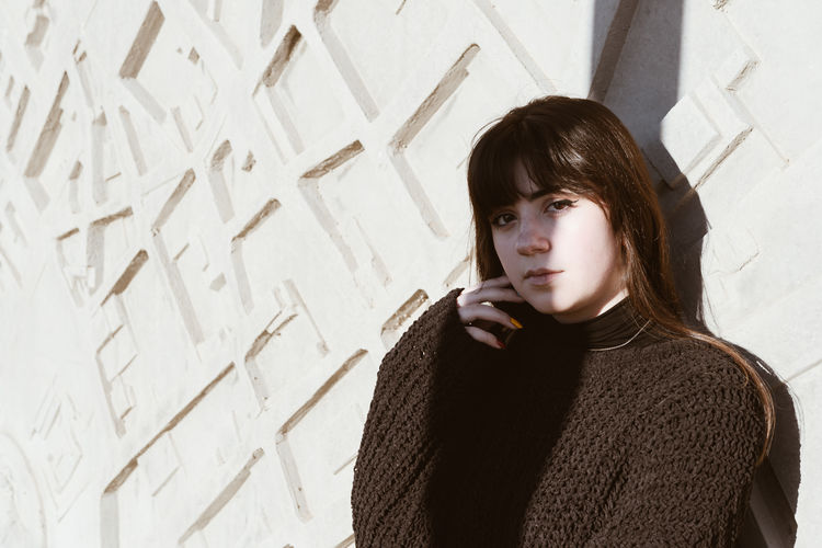 One Person Portrait Sweater Young Adult Front View Casual Clothing Wall - Building Feature Contemplation Young Women Indoors  Brown Hair Lifestyles Looking At Camera Real People Leisure Activity Headshot Hairstyle Standing Waist Up Warm Clothing Beautiful Woman Teenager Turtleneck Bangs
