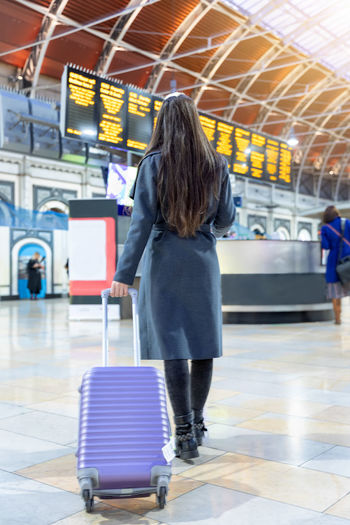 Traveler woman with a suitcase in a train station checks the departure times of the trains Rear View Travel Full Length Indoors  Transportation Real People Airport Luggage Suitcase Journey One Person Mode Of Transportation Women Casual Clothing Leisure Activity Waiting Train Station Timetable Woman Traveler Travel Train Rear View Hairstyle Departure Delay