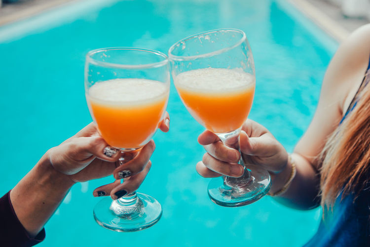 Adult Alcohol Celebratory Toast Drink Drinking Drinking Glass Food And Drink Friendship Glass Hand Holding Household Equipment Human Body Part Human Hand People Refreshment Smiling Swimming Pool Togetherness Turquoise Colored Two People Women