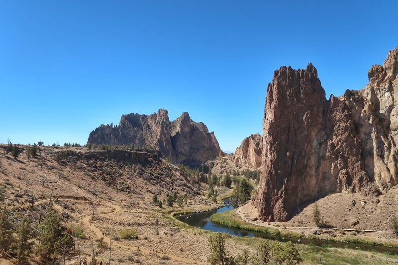 Landscape of a river running through a small valley against tall vertical rock formations at Smith Rock State Park in Oregon Smith Rock State Park Riverscape River Travel Destinations Rock Formations Oregon Sky Clear Sky Plant Blue Nature Copy Space Tranquility Non-urban Scene Day Landscape Sunlight Environment Succulent Plant Cactus Growth No People Scenics - Nature Tranquil Scene Beauty In Nature Land