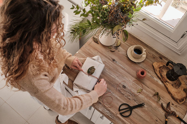 High angle view of woman sitting on table at home