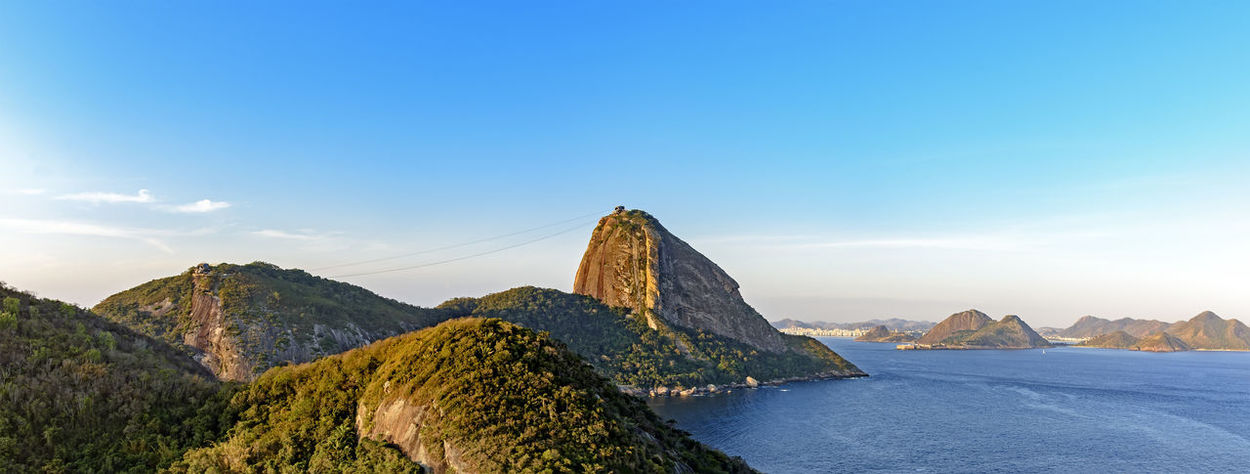 Panoramic image with sugarloaf hill, Rio de Janeiro mountains and Guanabara bay entrance Brazil Coastline Nature Rio De Janeiro Skyline Beauty In Nature Blue Forest Guanabara Bay Horizon Over Water Mountain Mountain Range Nature No People Ocean Outdoors Panoramic Landscape Physical Geography Scenics Sea Sky Sugarloaf Tranquil Scene Tranquility Water