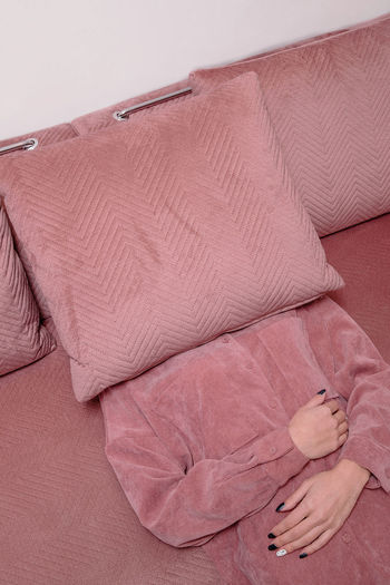 Midsection of person relaxing on bed at home