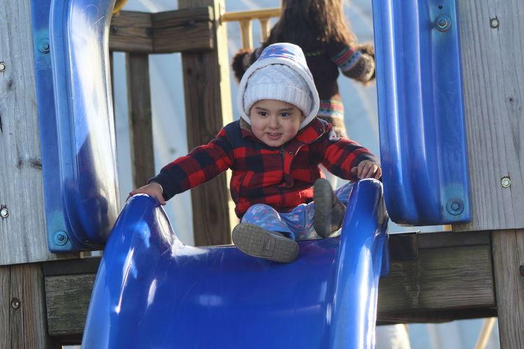 Full Length Of Boy Playing On Slide At Park