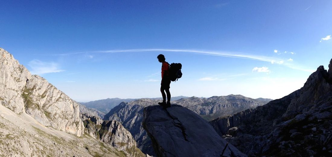 Side view of male hiker standing on mountain against blue sky