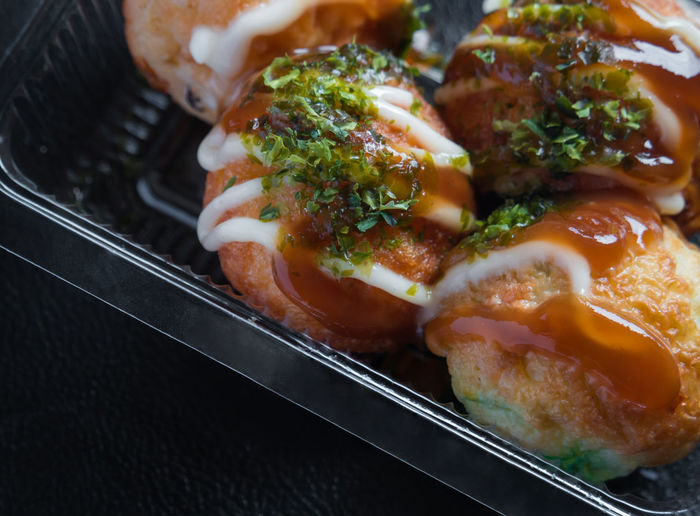 Close-up of takoyaki in container on table