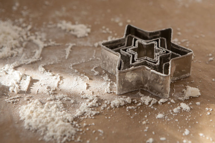 High Angle View Of Star Shaped Cookie Cutters And Flour On Table