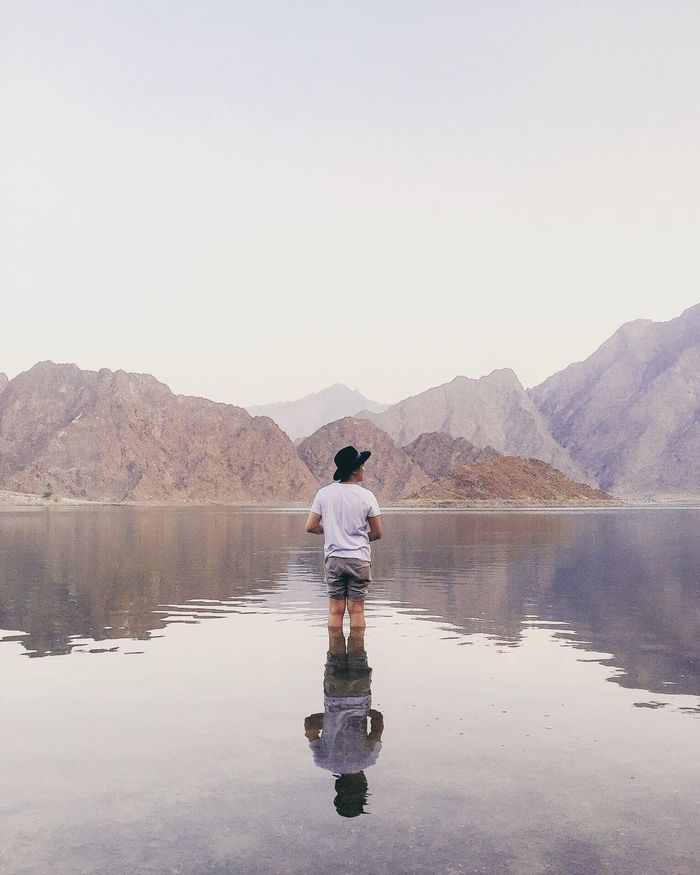 Rear view of man standing in lake against mountains