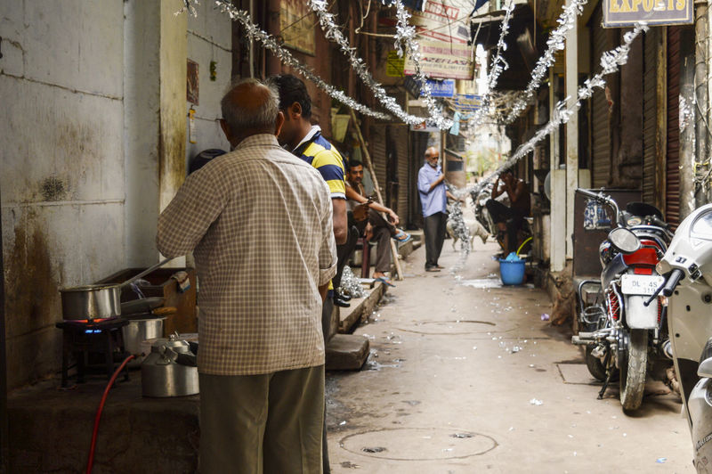 Rear view of people on street amidst buildings in city