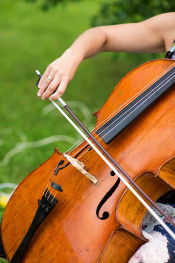 Cropped hand of woman playing violin at park