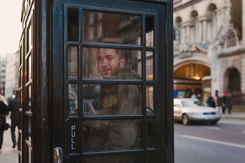 Portrait of man standing inside telephone booth