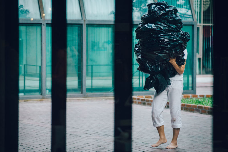 Man carrying garbage bags while walking on footpath seen through gate