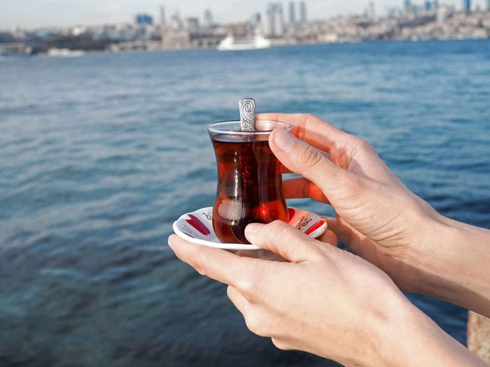 Close-up of hand holding glass of tea in turkey istanbul above of sea