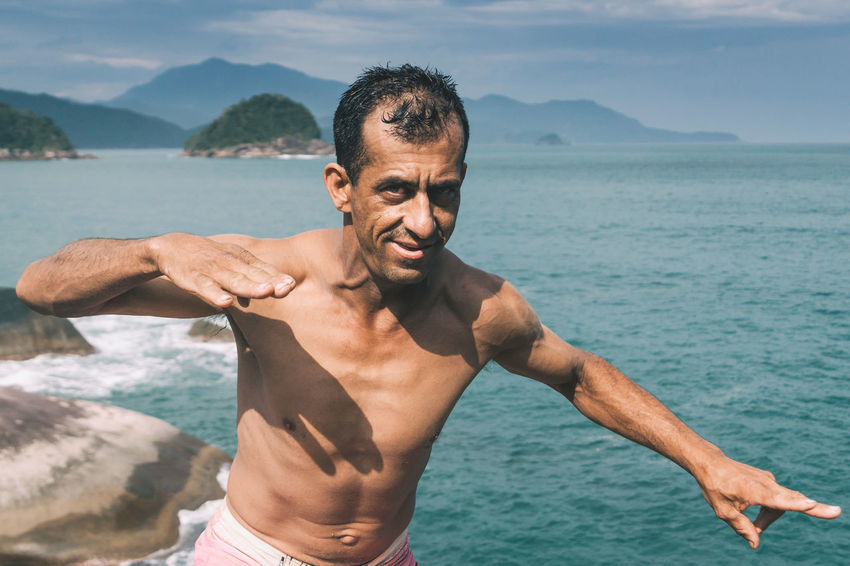 The jungle master - I tried to get up the highest rock - but I couldn't find a way to get up there.. Until this guy showed me how to do it! Body & Fitness Brasileiro Day Gesture Happiness Jungle Lifestyles Looking At Camera Men Mountain Mountain Range Nature One Person Outdoors People Portrait Real People Sea Shirtless Shirtless Smile Smiling The Portraitist - 2017 EyeEm Awards Water Young Adult BYOPaper! This Is Masculinity