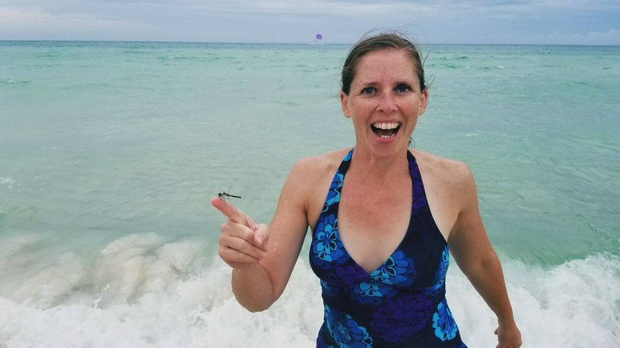 Portrait Of Smiling Woman With Dragonfly On Index Finger Standing At Beach