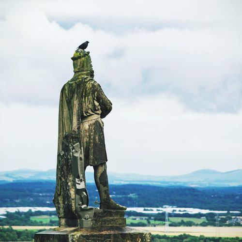 Raven Perching On Old Statue Of Robert The Bruce At Stirling Castle