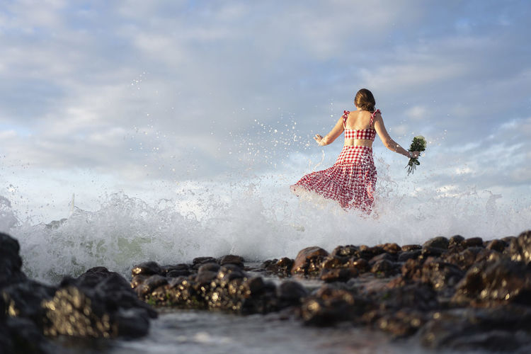 Woman on rock in sea against sky