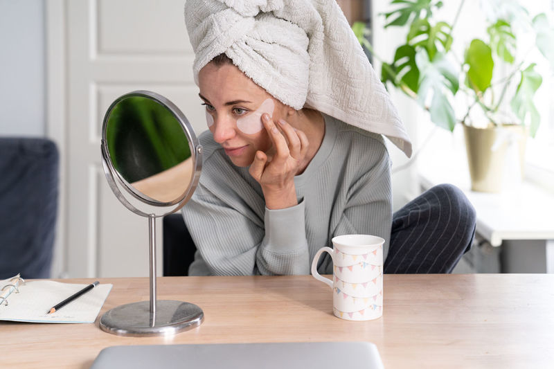 Woman applying beauty product by mirror on table