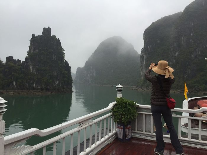 Rear View Of Woman Standing Against Rock Formations At Halong Bay