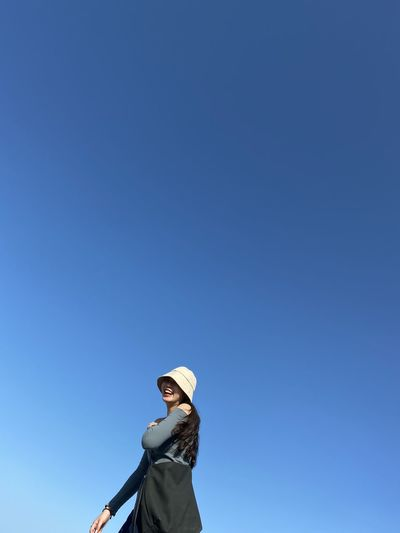 Low angle view of woman wearing sunglasses against clear blue sky
