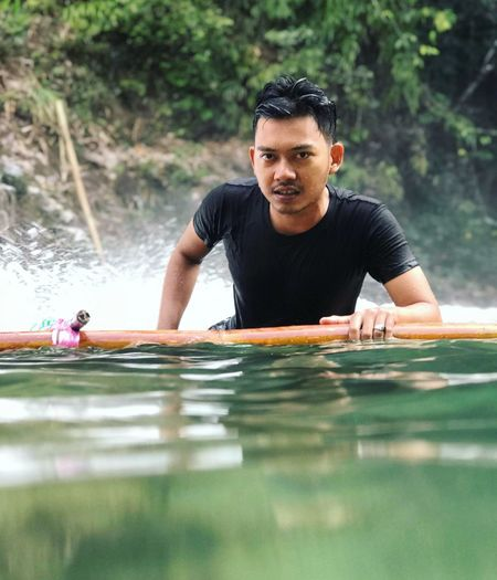Portrait of young man on wooden raft in river
