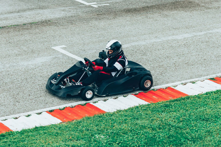 Woman Driving Go-Cart Go-carting Carting Champ Car Racing Soapbox Chart Chart Car Competitive Sport Motorsport Driver Drive Speed Sport Sport Race Motor Racing Track Activity Young Woman Driving Sports Uniform Sports Helmet Lifestyle Car Racing Fun Outdoors High Angle View