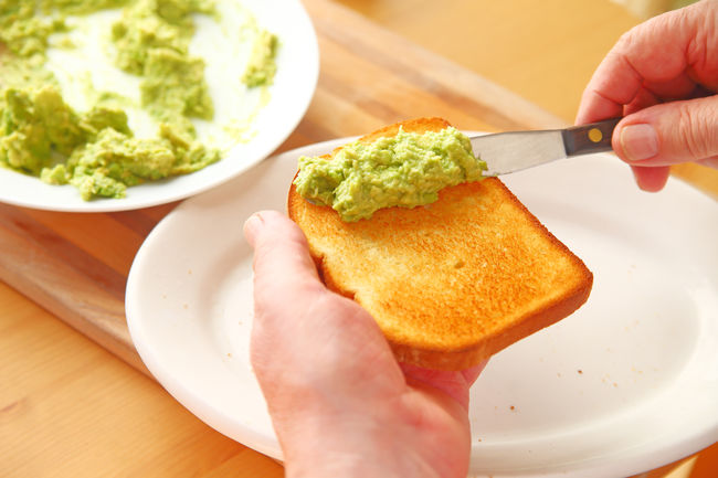 Man makes avocado toast point of view Bowl Breakfast Day Fingers Freshness Green Hands Healthy Eating Holding Home Food Indoors  Man Mashed Food Natural Light One Person Point Of View Snack Spreading Textures Trendy Food Using Tool Vegetables White Platter Wood Surface