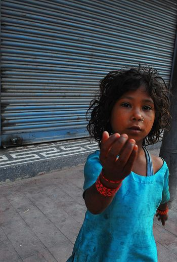 Unidentified A Young woman in Nepal. She is a beggar kid begging for money. EyeEmNewHere Architecture Casual Clothing Child Childhood Curly Hair Day Females Front View Hair Hairstyle Innocence Iron Leisure Activity Lifestyles Looking At Camera One Person Outdoors Portrait Real People Standing Women