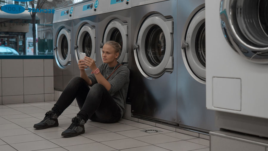 Full length of woman using mobile phone while sitting by washing machine