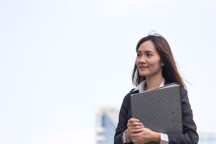 Businesswoman looking away while holding file