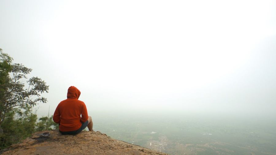 Man sitting on rock against sky during foggy weather